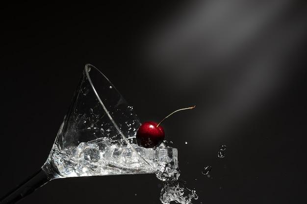 Nahaufnahme des spritzwassers mit fallender kirsche. Premium Fotos
