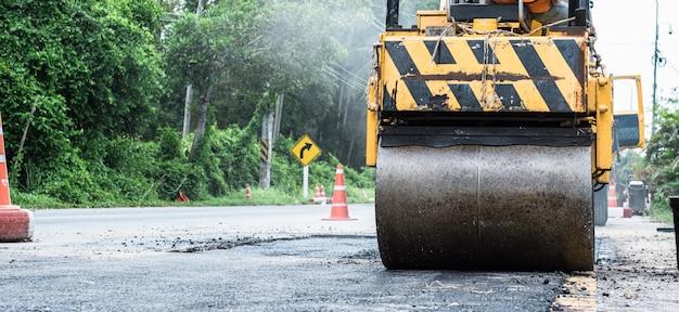 Nahaufnahme des stahlrades einer kleinen asphaltrolle herein im dienst reparierend, asphaltstraße reparierend. arbeiter auf einem straßenbau, industrie und teamarbeit. Premium Fotos