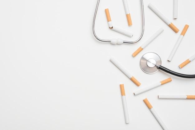 Nahaufnahme des stethoskops und der zigaretten, die ein rauchendes thema vorschlagen Kostenlose Fotos