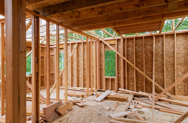 Nahaufnahme des strahls errichtete nach hause im bau und blauen himmel mit hölzernem binder-, beitrags- und strahlrahmen. holzrahmenhaus, immobilienhintergrund Premium Fotos