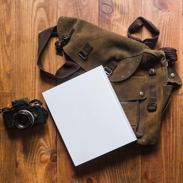 Nahaufnahme des tagebuchs und der tasche mit kamera auf hölzernem schreibtisch Kostenlose Fotos