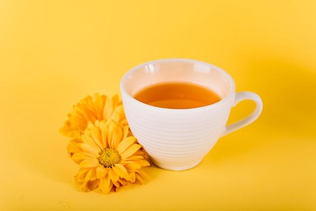 Nahaufnahme des tees und der blumen auf gelbem hintergrund Kostenlose Fotos