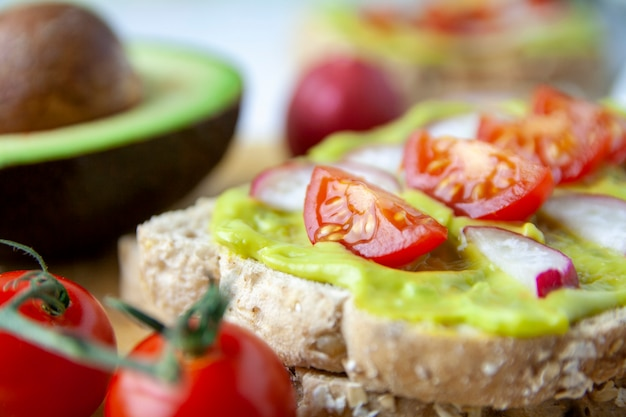 Nahaufnahme des toasts mit avocado, rettich und tomate Premium Fotos