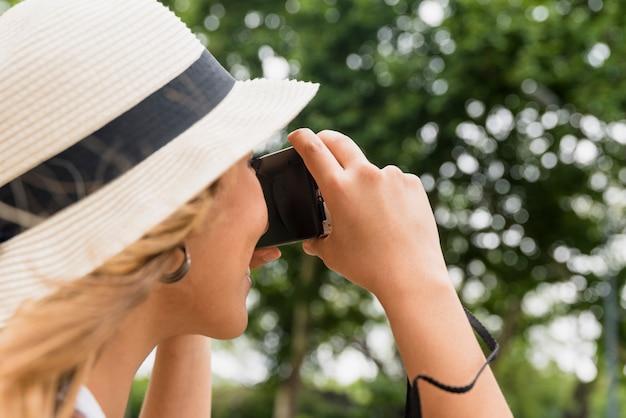 Nahaufnahme des tragenden hutes der jungen frau, der foto von der kamera macht Kostenlose Fotos