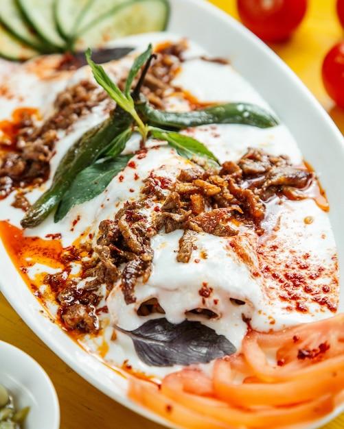 Nahaufnahme des türkischen ikender-kebabs, der mit saurem joghurt auf weißem teller serviert wird Kostenlose Fotos