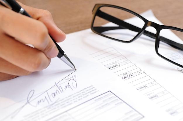 Nahaufnahme des unterzeichnenden dokuments der person Kostenlose Fotos