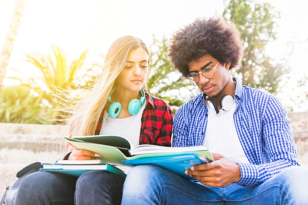 Nahaufnahme des verschiedenen jungen mannes und der studentin, die das buch liest Kostenlose Fotos