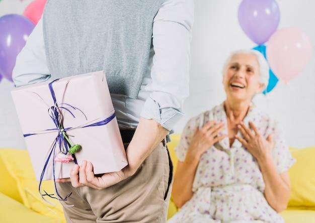 Nahaufnahme des versteckenden überraschungsgeburtstagsgeschenkes des mannes von seiner glücklichen frau Kostenlose Fotos