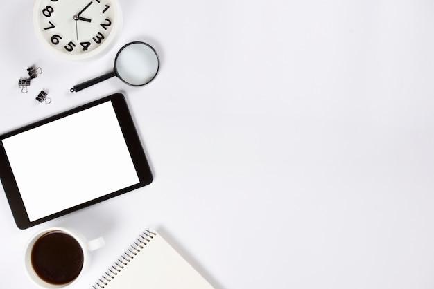 Nahaufnahme des weckers; vergrößerungsgläser; digitales tablett; kaffeetasse und notizblock auf weißem hintergrund Kostenlose Fotos