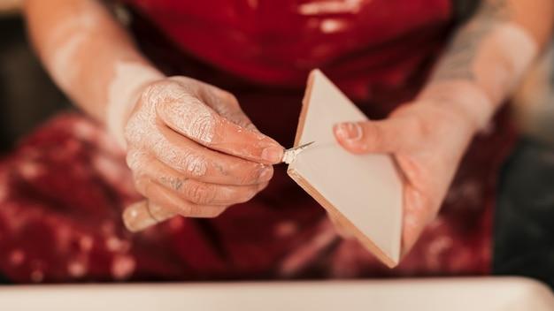 Nahaufnahme des weiblichen töpfers die farbe auf fliesen mit scharfem werkzeug säubernd Kostenlose Fotos