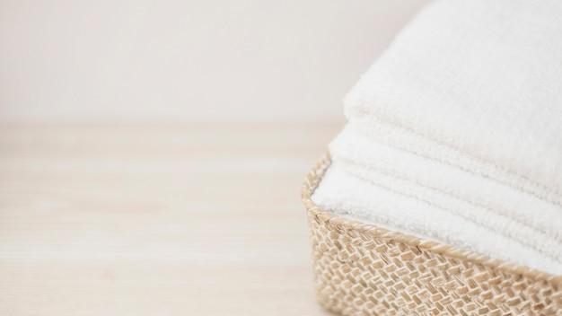 Nahaufnahme des weidenkorbes mit gestapelten tüchern Kostenlose Fotos