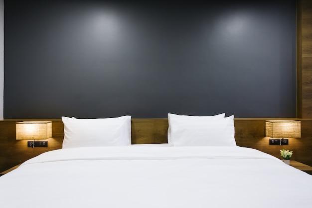 Nahaufnahme des weißen kissens auf bettdekoration mit heller lampe im hotelschlafzimmerinnenraum. Premium Fotos