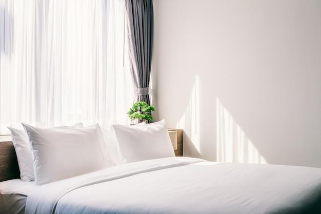 Nahaufnahme des weißen kissens auf bettdekoration mit heller lampe und grünem baum Premium Fotos