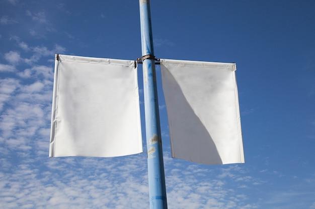 Nahaufnahme des weißen laternenpfahl-fahnenplakats gegen blauen himmel Kostenlose Fotos