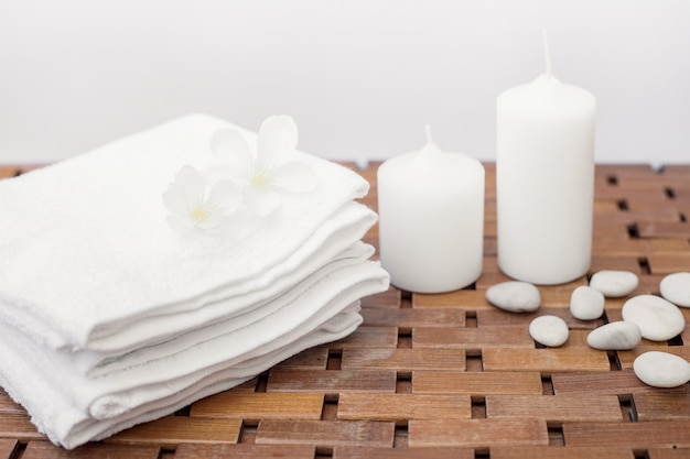 Nahaufnahme des weißen tuches; blumen; kerzen und kieselsteine auf holztisch Kostenlose Fotos