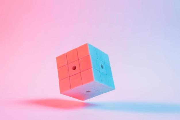 Nahaufnahme des würfels 3d des puzzlespiels auf rosa hintergrund Kostenlose Fotos