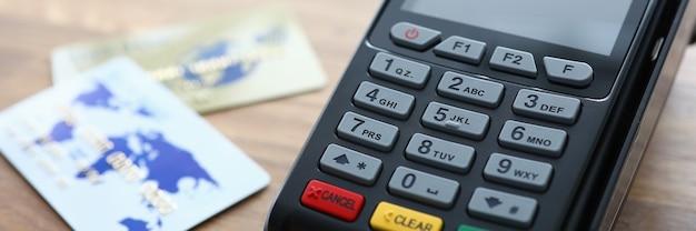 Nahaufnahme des zahlungsterminals und der kreditkarten auf holztisch. moderner kartenleser zum online-bezahlen. kaufen und verkaufen sie produkte oder dienstleistungen. technologiekonzept Premium Fotos