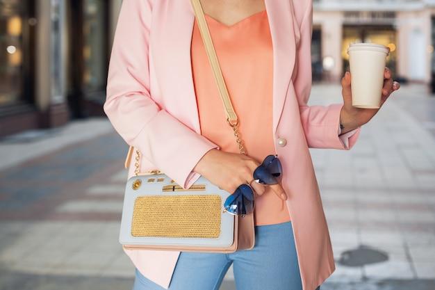 Nahaufnahme details der accessoires der frau in stilvoller kleidung, auf der straße spazieren gehen, sonnenbrille, handtasche, rosa jacke, trendige farben, frühling sommer sommer modetrend, eleganter stil, kaffee trinken Kostenlose Fotos