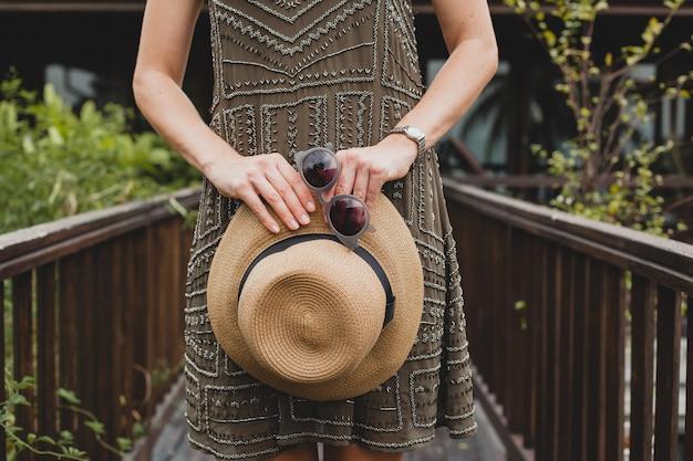 Nahaufnahme details hände halten strohhut und sonnenbrille, stilvolle accessoires, junge attraktive frau in elegantem kleid, sommerstil, modetrend, urlaub, posiert auf tropische villa, lächelnd, glücklich Kostenlose Fotos