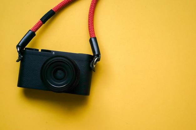 Nahaufnahme draufsicht einer schwarzen kamera mit roten riemen und copyspace Premium Fotos
