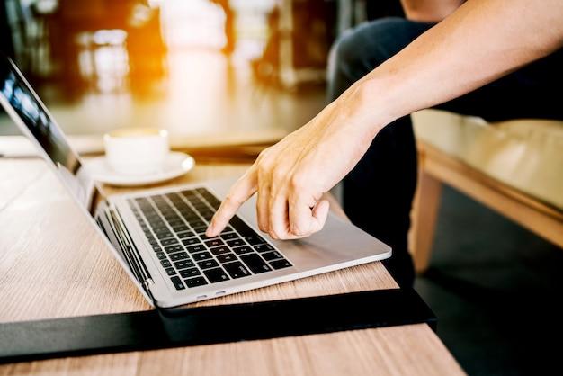 Nahaufnahme ein mannfinger, der einen knopf einer laptoptastatur drückt, während er zu hause sitzt und arbeitet Premium Fotos