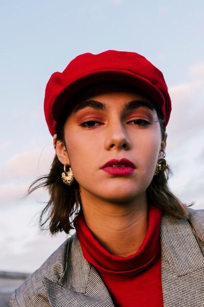 Nahaufnahme einer attraktiven jungen frau in der roten kappe, die kamera betrachtet Kostenlose Fotos