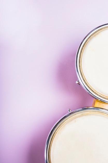 Nahaufnahme einer erhöhten ansicht der bongotrommel auf purpurrotem hintergrund Kostenlose Fotos