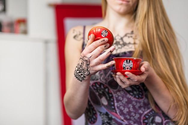 Nahaufnahme einer frau, die chinesischen tee in einer traditionellen teezeremonie hält Kostenlose Fotos
