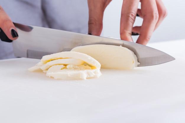 Nahaufnahme einer frau, die den käse mit messer auf weißer tabelle schneidet Kostenlose Fotos