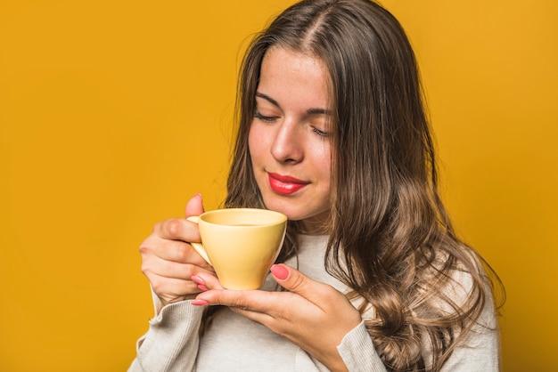 Nahaufnahme einer frau, die den kaffee von der gelben schale riecht Kostenlose Fotos