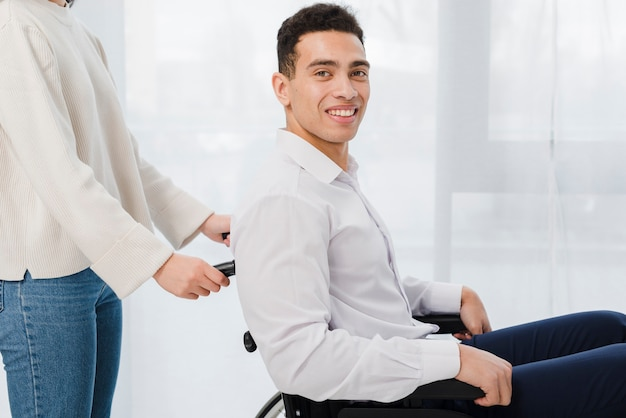 Nahaufnahme einer frau, die den lächelnden jungen mann sitzt auf rollstuhl drückt Kostenlose Fotos