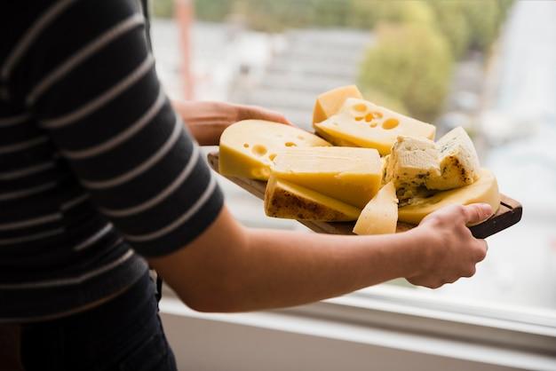 Nahaufnahme einer frau, die hölzernes hackendes brett mit käsescheiben hält Kostenlose Fotos