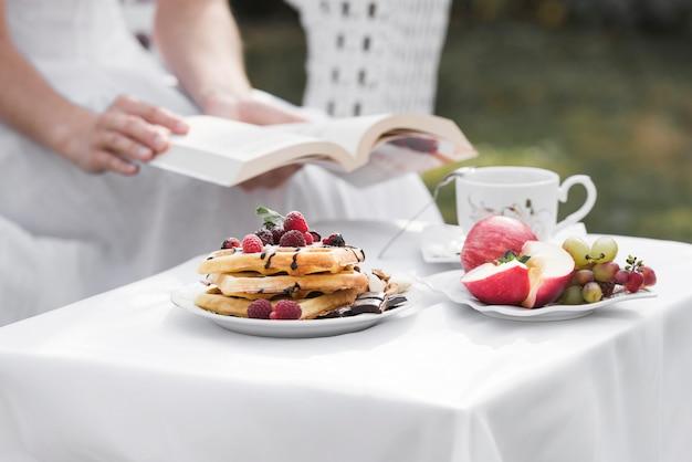 Nahaufnahme einer frau, die in der hand das buch sitzt hinter dem frühstückstisch an draußen hält Kostenlose Fotos