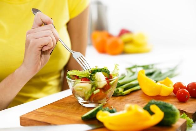 Nahaufnahme einer frau, die salat in der küche isst Kostenlose Fotos