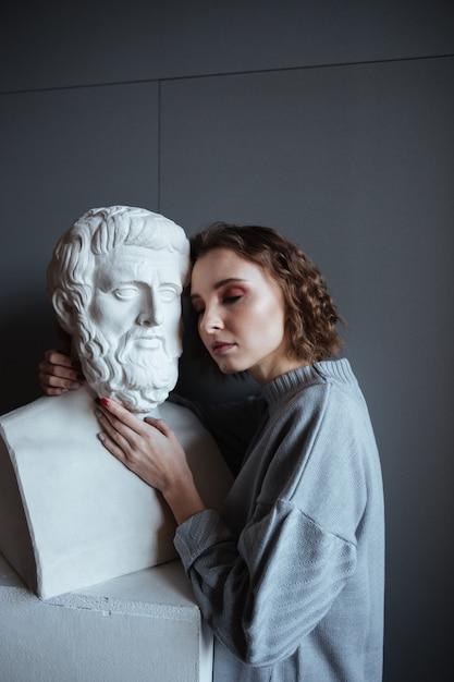 Nahaufnahme einer frau, die sich auf eine marmorbüste stützt Kostenlose Fotos