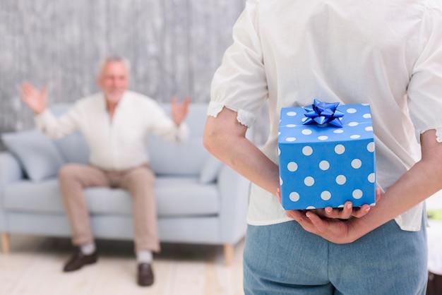 Nahaufnahme einer frau, die zurück geschenkbox hinter ihr versteckt, überraschend ihren ehemann Kostenlose Fotos