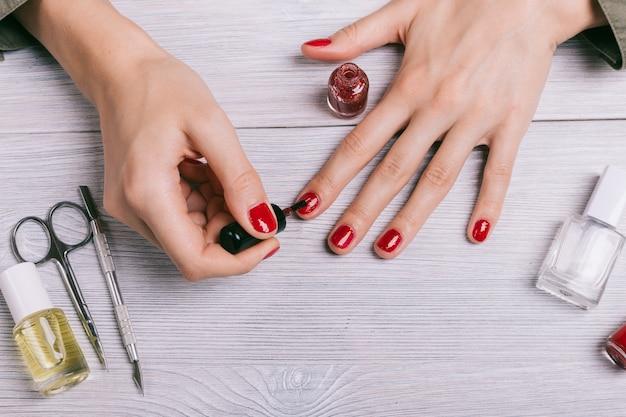 Nahaufnahme einer frau malt ihre nägel mit rotem lack Premium Fotos
