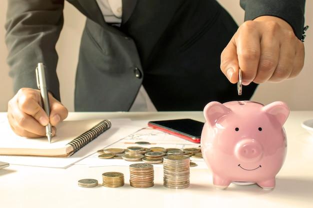 Nahaufnahme einer geschäftsfrau, die eine münze in einem sparschwein hält, ein konzept des geldsparens für die finanzbuchhaltung. Premium Fotos