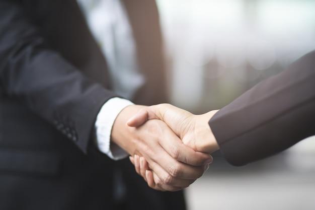 Nahaufnahme einer geschäftsmannhanderschütterungsgeschäftsfrau zwischen zwei kollegen ok Premium Fotos
