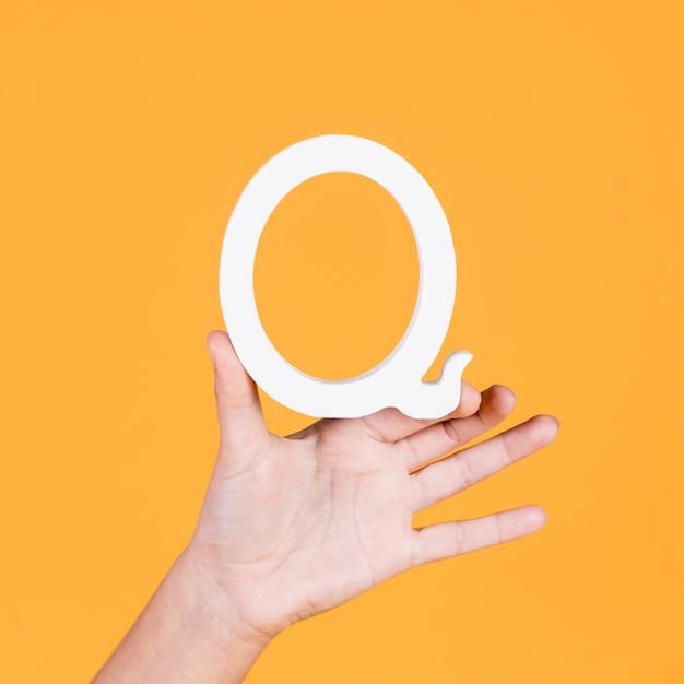 Nahaufnahme einer hand, die den buchstaben q hält Kostenlose Fotos