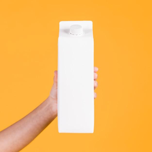 Nahaufnahme einer hand, die weißen tetrapack gegen gelbe oberfläche hält Kostenlose Fotos