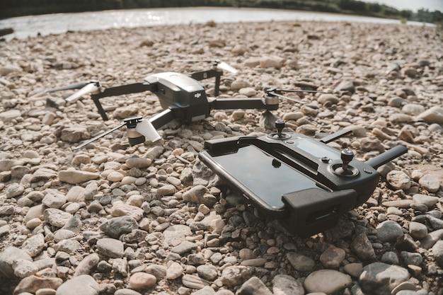 Nahaufnahme einer high-tech-drohne und ihres fernbedienungsgeräts auf grauen kieselsteinen Kostenlose Fotos
