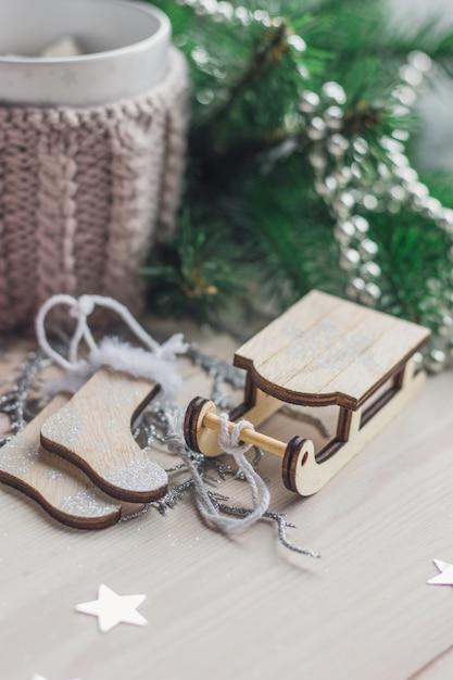 Nahaufnahme einer hölzernen schlittenverzierung, die durch weihnachtsdekorationen auf dem tisch umgeben ist Kostenlose Fotos