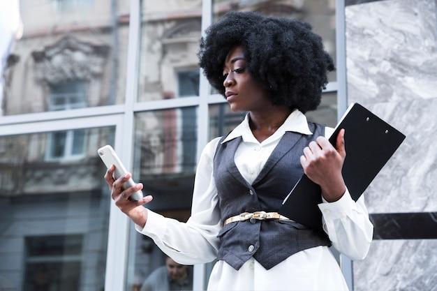 Nahaufnahme einer jungen afrikanischen geschäftsfrau, die klemmbrett unter verwendung des handys hält Kostenlose Fotos