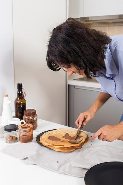 Nahaufnahme einer jungen frau, die die erdnussbutter auf pfannkuchen mit messer und löffel verbreitet Kostenlose Fotos