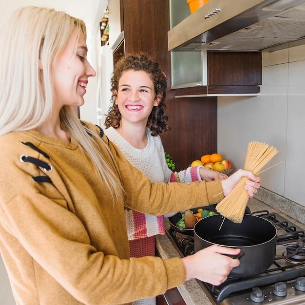 Nahaufnahme einer jungen frau, die spaghettis im topf mit ihrer freundin kocht Kostenlose Fotos