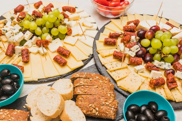 Nahaufnahme einer käseplatte mit trauben, oliven und geräucherten würsten auf schieferbrett Kostenlose Fotos