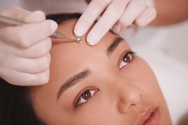 Nahaufnahme einer kosmetikerin mit mitesserentferner auf dem gesicht einer kundin zugeschnitten Premium Fotos