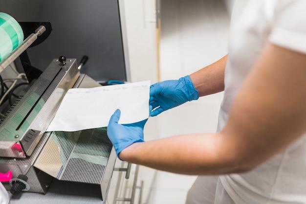 Nahaufnahme einer krankenschwesterhand, die an beuteleichmeister-verpackungsmaschinerie arbeitet Kostenlose Fotos