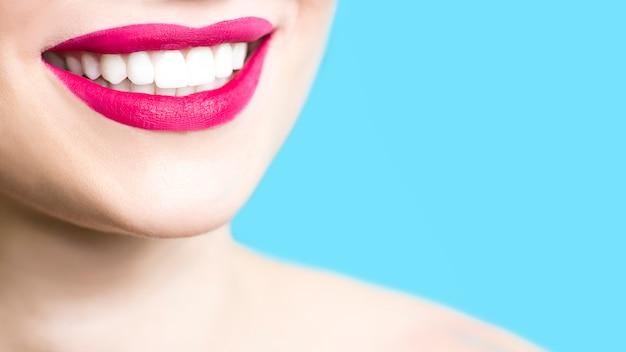 Nahaufnahme einer lächelnden frau mit den gesunden weißen zähnen, roter lippenstift, saubere haut. Premium Fotos